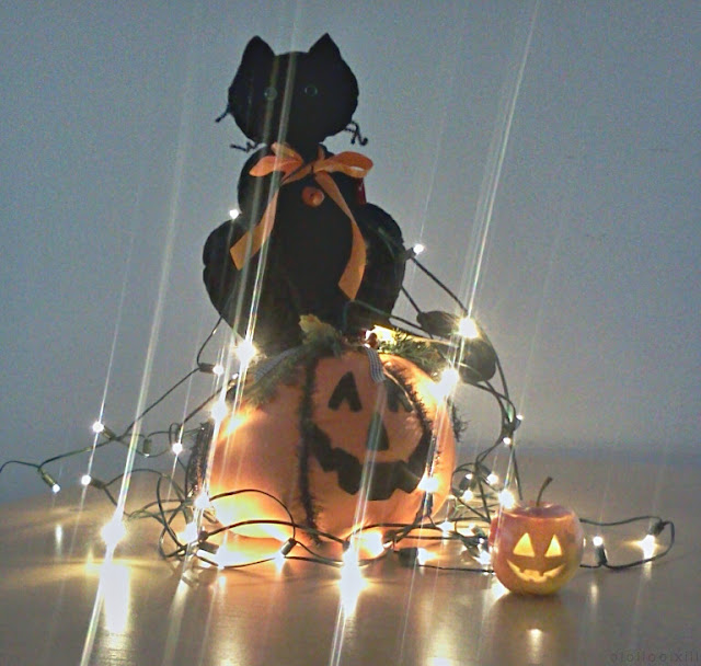 A sad looking selection of Halloween decorations and lights; featuring a cat sitting on a pumpkin.