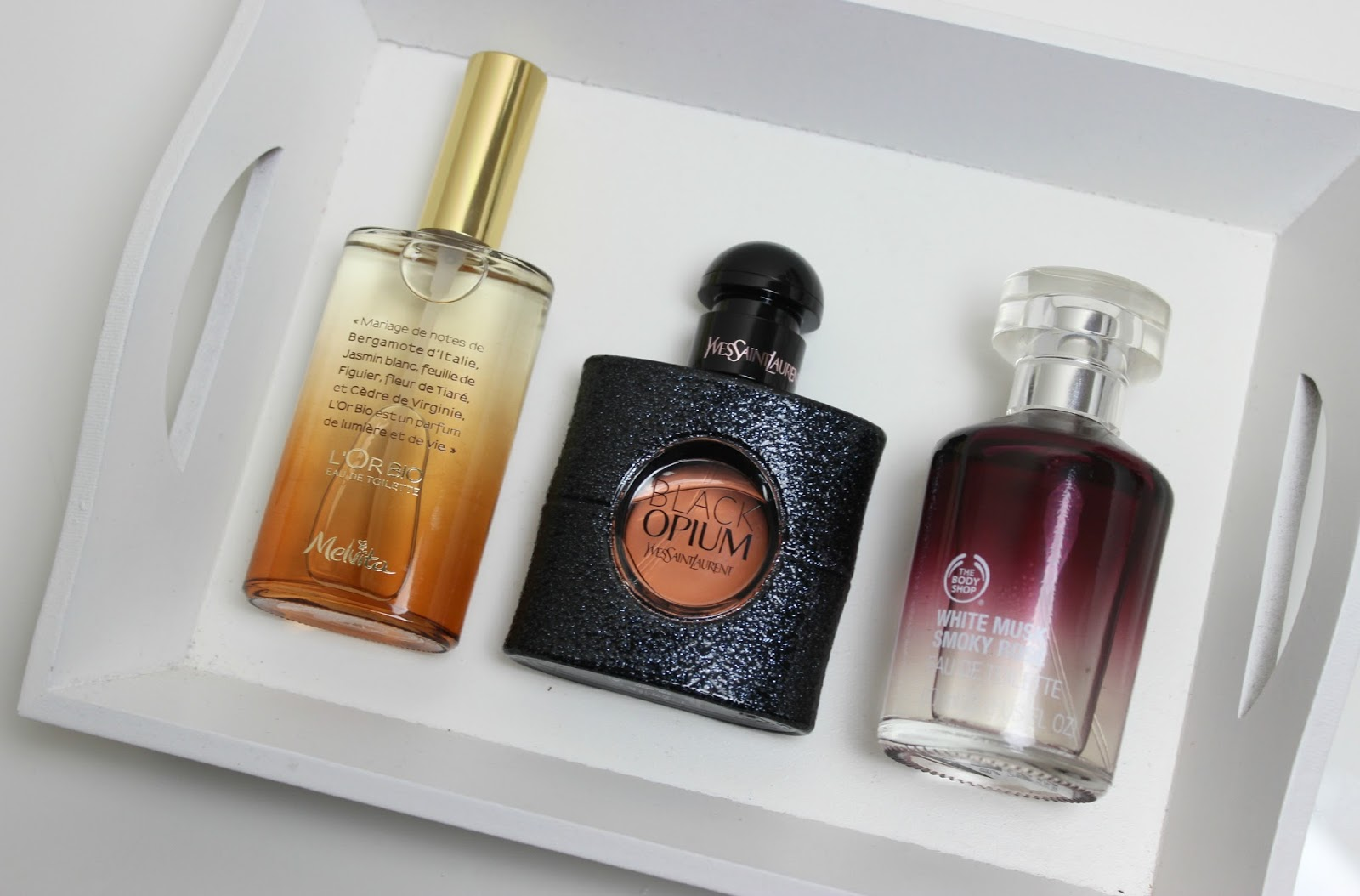 A picture of Melvita L'Or Bio Eau de Toilette, YSL Black Opium and The Body Shop White Musk Smoky Rose Eau de Parfum
