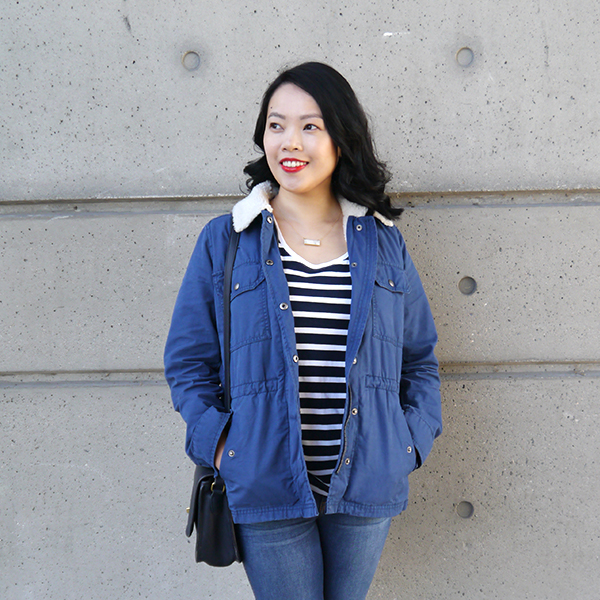 Vancouver beauty, life, and style blogger Solo Lisa wears a blue sherpa-lined utility jacket with a fuzzy shearling collar, navy and white striped tee, blue skinny jeans, a gold and howlite marble necklace, red lipstick, and a vintage bag.
