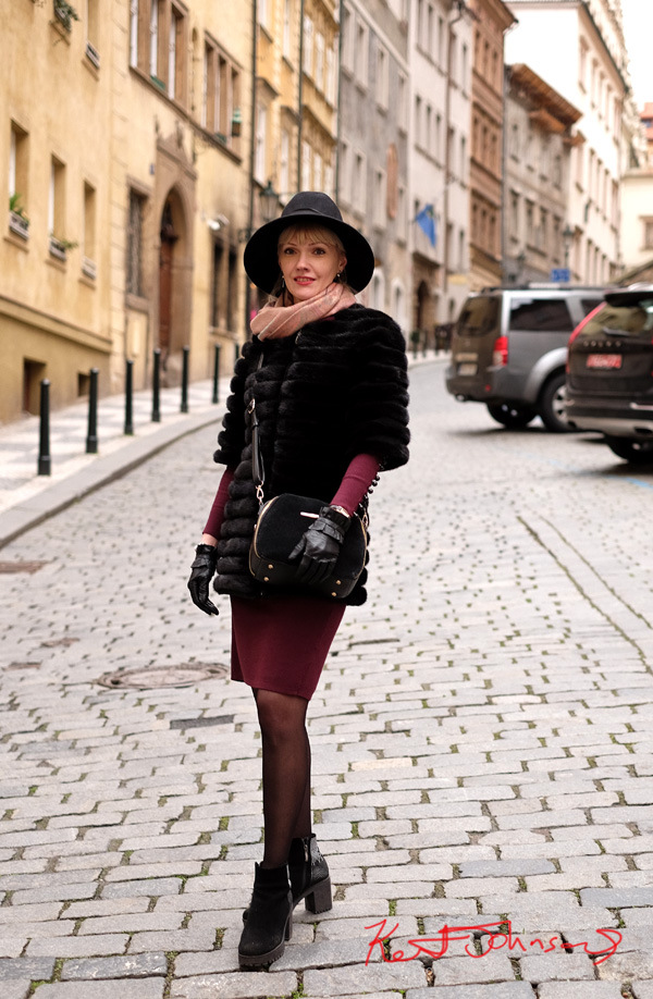 A woman in a black short sleeve fur jacket, leather gloves, purple skirt and long sleeve top with nude scarf and large black hat. Street Fashion in Prague photographed by Kent Johnson.