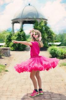 Girl in pink tutu dancing outdoors