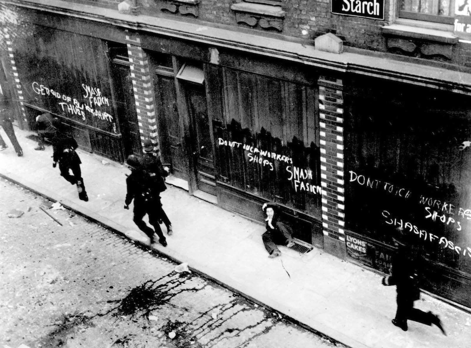 Policemen chasing Communist counter-demonstrators at a Fascist demonstration near Mark Lane, London. 1936.