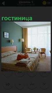 Показан номер в гостинице с кроватью, сумка, белье и большое окно