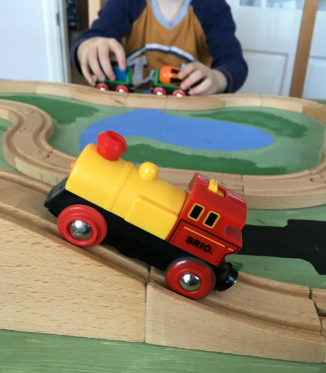 close-up-of-Brio-Battery-operated-action-train-with-boy-playing-with-cement-mixer-and-coal-truck-in-the-background