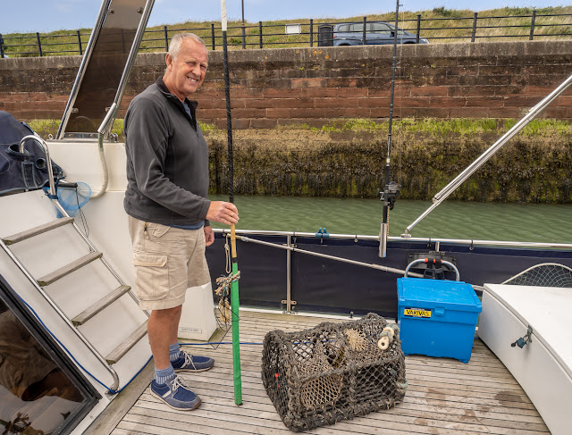 Photo of Phil with our new-to-us lobster pot and flag pole