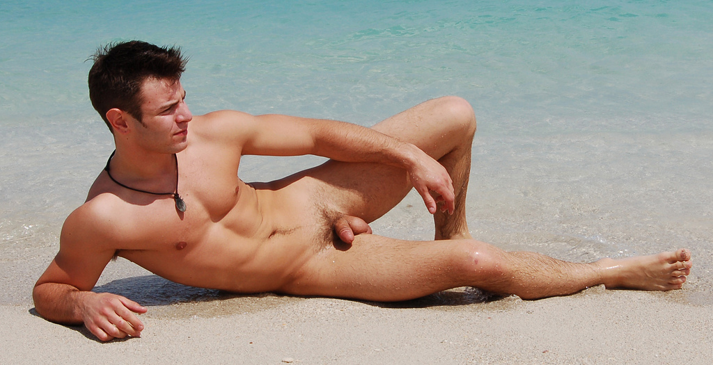 A playful sexy and hairy man poses on the beach