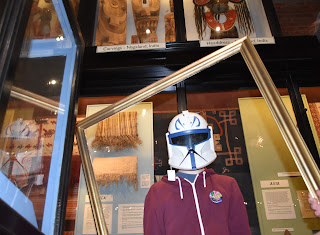 Photograph of young person in a frame wearing a star wars mask and standing in front of a museum case.
