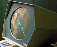 Fotografía de una pantalla circular en la que aparecen puntos y rayas de colores. Se trata de Spacewar! corriendo en un ordenador analógico PDP-1 en 1962