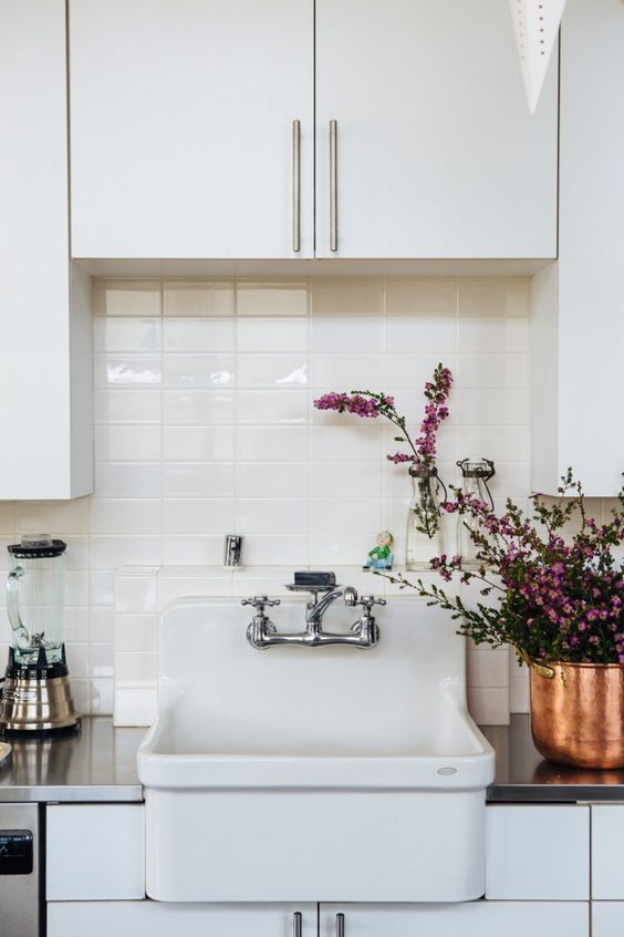 Simple and spare modern farmhouse sink in kitchen with tile backsplash