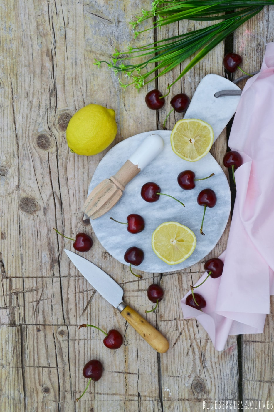 ingredients of cherry lemonade, wood handle knife and wood squeezer,lemons and cherries, cutting white marble board over old wood table