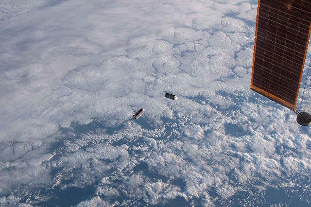 Hai vệ tinh của dự án Planet đang trôi lơ lửng bên dưới tấm pin năng lượng Mặt Trời của Trạm Không gian Quốc tế (ISS). Hình ảnh: NASA.
