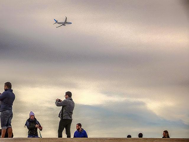 Gente tomando fotografías y sobre ellos avión volando en las alturas
