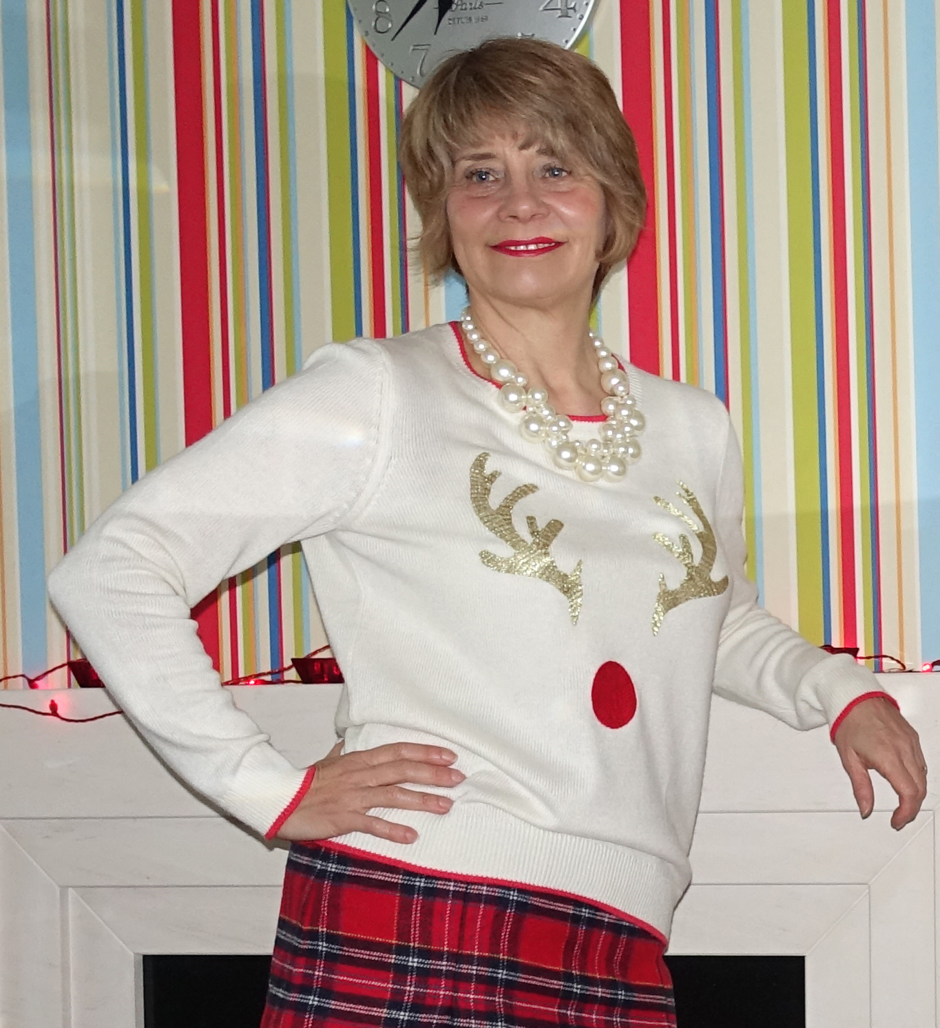 Image showing a middle aged woman indoors wearing a cream Christmas jumper embellished with reindeer antlers and a red tartan skirt