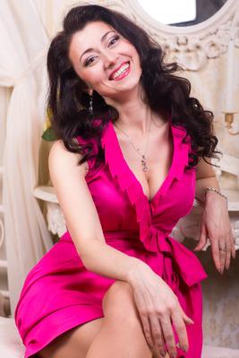 Marina, eine Frau aus der Ukraine. Portraitfoto im Kleid. Farbe Pink