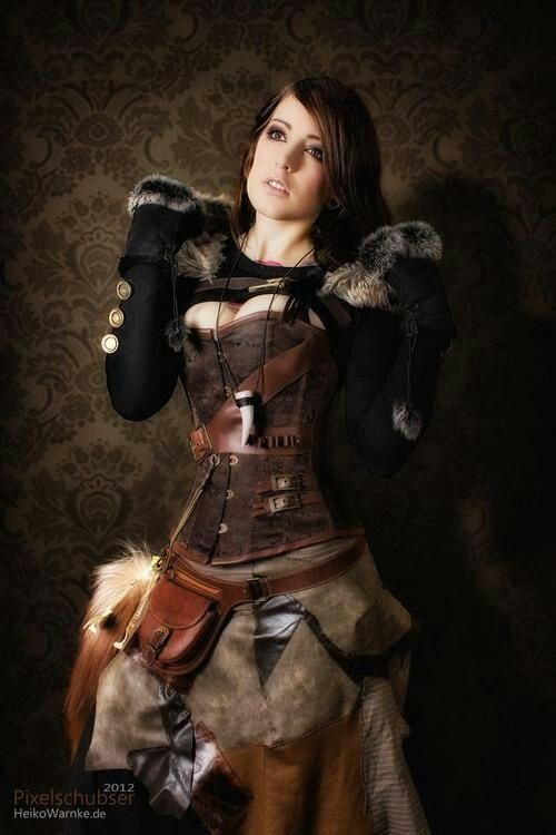 Steampunk woman in shrug with fur collar and sleeves, and fox tail, with patwork skirt and overbust corset. Women's steampunk clothing.