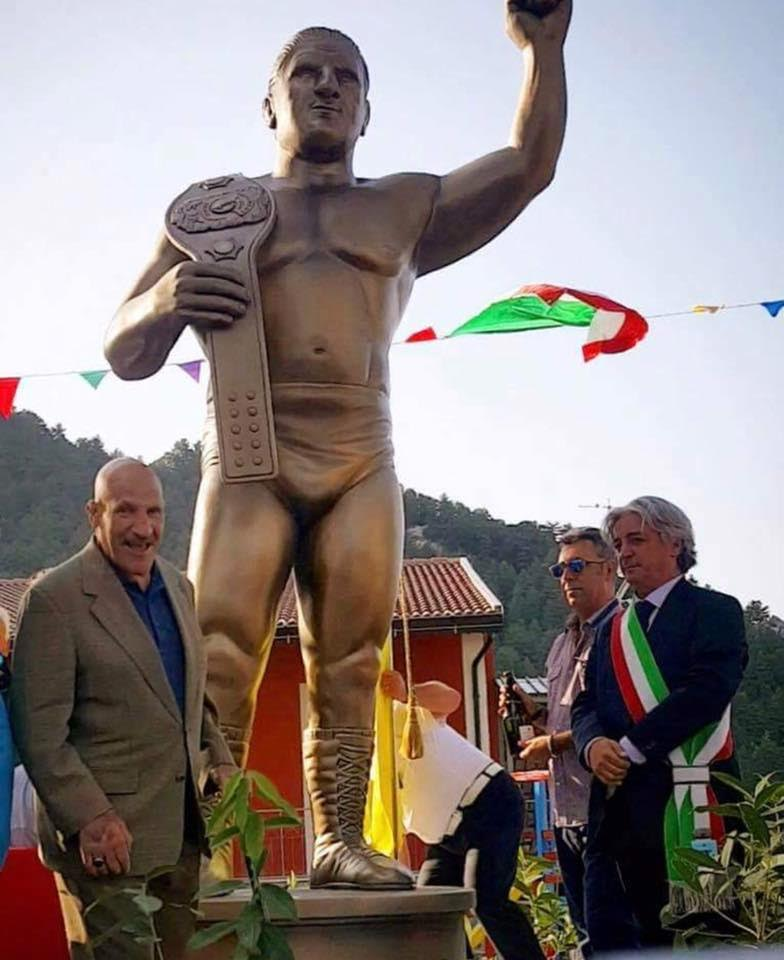 Bruno Sammartino posing with a statue in his honor in his birth home of Pizzoferrato, Italy. StrengthFighter.com