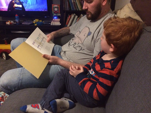 Little boy and his daddy reading the book