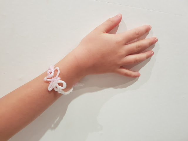 A child's hand on a white wall wearing a pink and white Gel-a-Peel bracelet