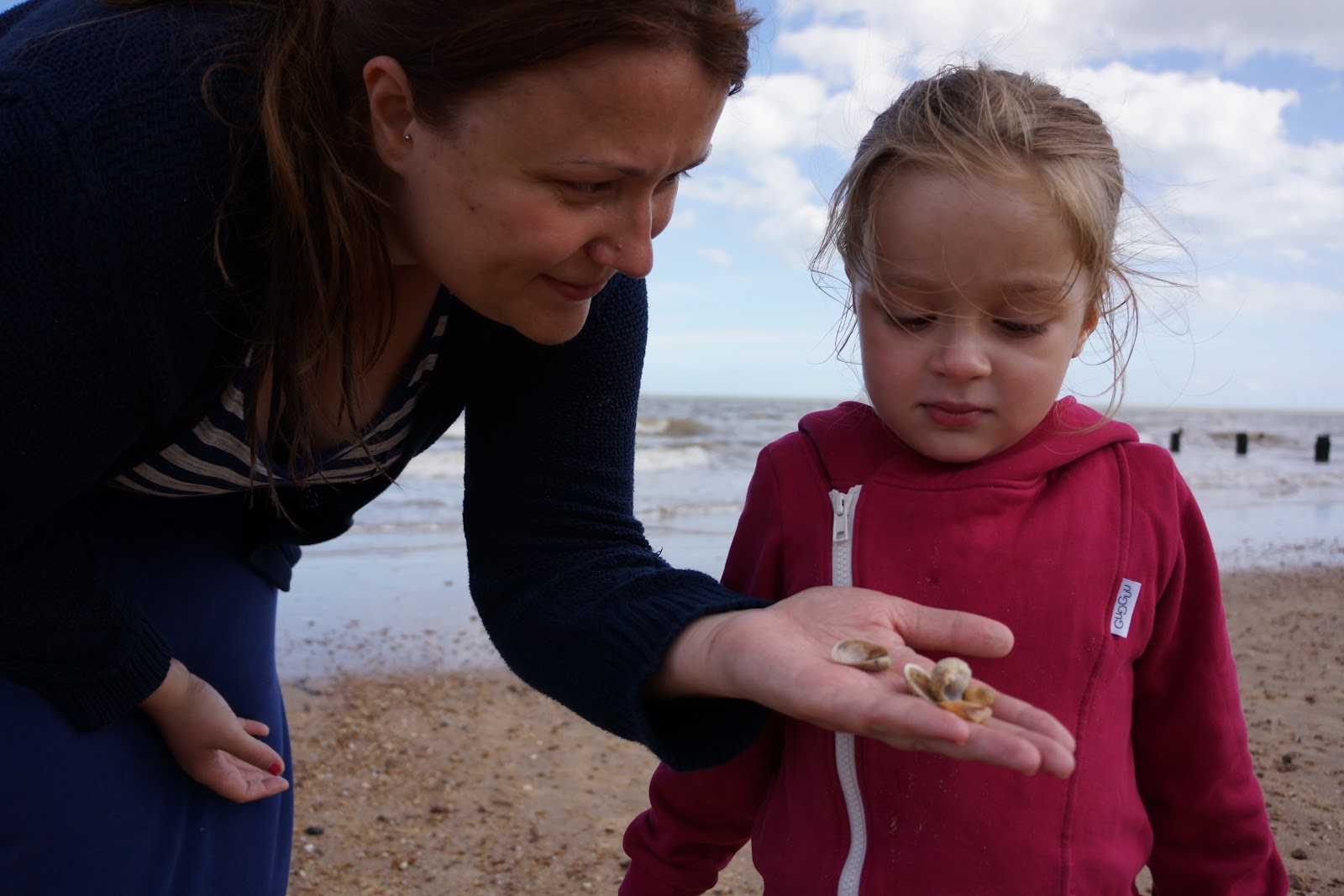 mum showing seashells to daughter