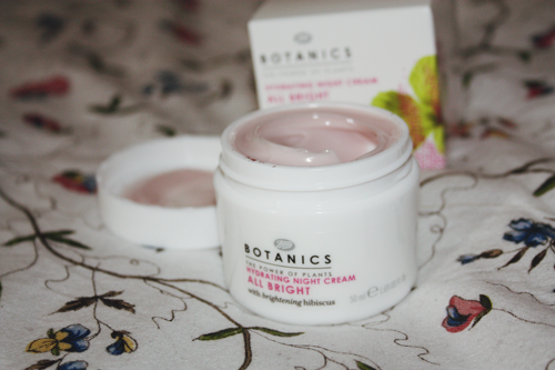 Botanics All Bright Hydrating Night Cream open in its pot, with the packaging behind it, on an IKEA duvet