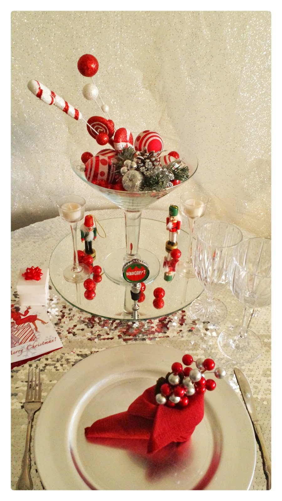 christmas table design using ornaments, sequin tablebloth, red napkins folded into elf shoe