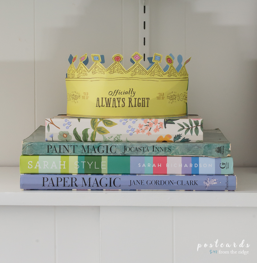 paper crown and colorful books on a shelf