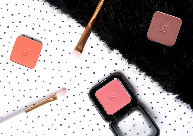 rectangular pans of red orange, pink, and muted purple eyeshadows sat on a black polka dot background