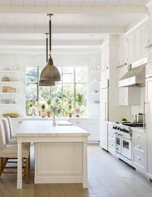Modern farmhouse style kitchen with white cabinets, vintage pendant lights over island, open shelving