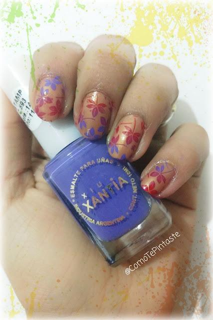 mano con base dorada y flores violetas y rojas sosteniendo esmalte xantia