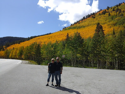 The peak of the fall colors along Monarch Pass with 2 people posing for a photo.