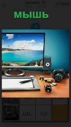 на столе стоит монитор, колонки и мышь