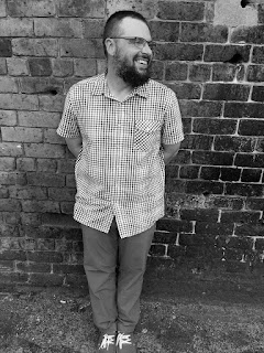 black-and-white photo of poet Peter Davis leaning against a brick wall