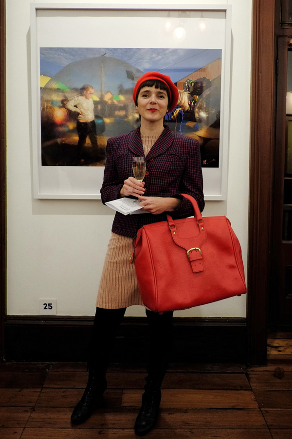 Code Red! Red beret, and oversized bag, vintage 1930's navy jacket with red-line check, black leggings and boots at Juniper Hall. Louise Whelan photograph in background. Street Fashion Sydney - Photographed by Kent Johnson.