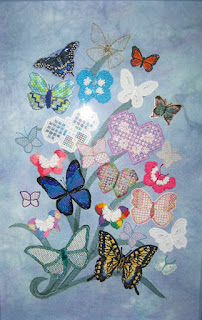colourful butterflies embroidered in a variety of techniques and fibres assembled on a blue mottled background with embroidered leaves and framed