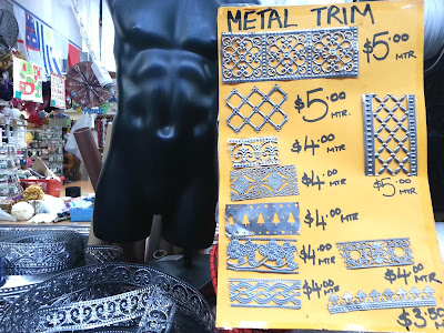 Poster displaying various metal trim pieces, with prices per metre, with lengths of the trims coiled on the table beside it.