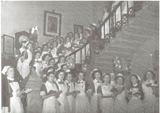 Photograph shows Adelaide Hospital nurses in uniform standing on the hospital staircase , 1950s