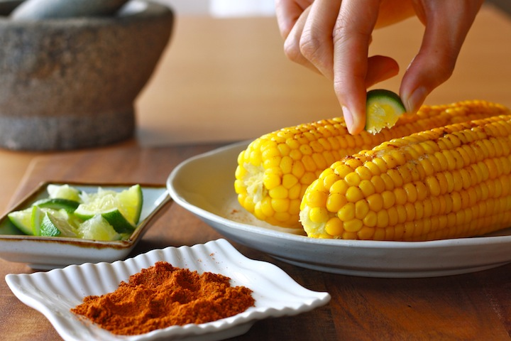 spice seasoning and fresh lime on corn on the cob