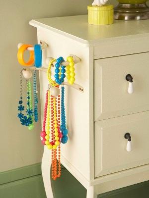 Pasang pengait kecil di sisi lemari atau meja untuk memajang kalung dan gelang-gelang.