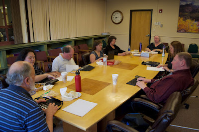 eight staff members seated around a table, most reading or writing in Braille