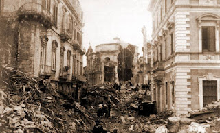 A devastated street in Messina with the remains of the Chiesa delle Anime del Purgatorio in the distance