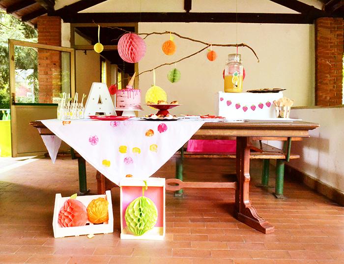 lo sweet table con sfondo di frutti pompom appesi ad un ramo sospeso