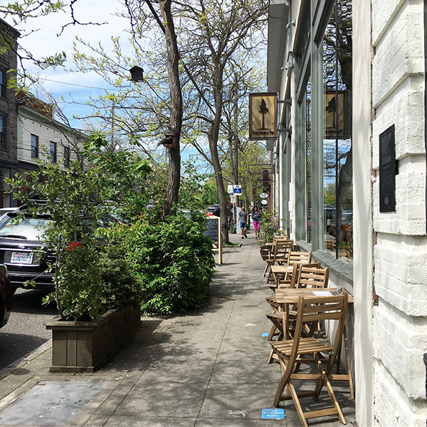A quiet street lined with greenery and sidewalk cafe tables in Ballard, Seattle