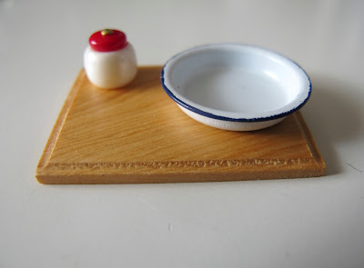 Dolls' house miniature chopping board with a enamelware bowl and red and cream jar on it.