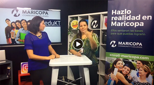 snapshot of Univision video; Claudia and Romy on set, surrounded by Maricopa Community Colleges posters