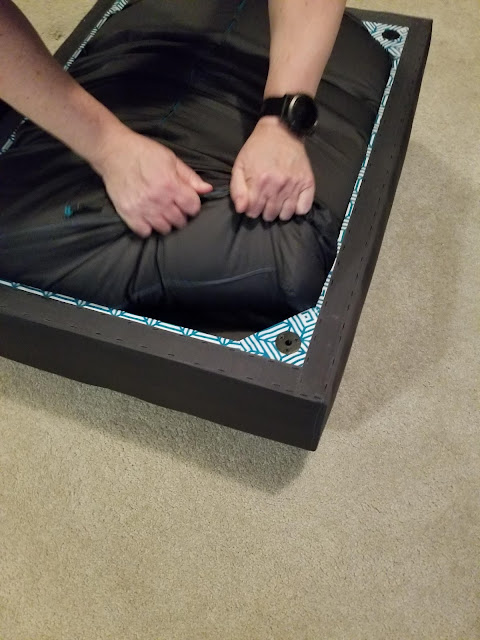 man removing lovesac love sac sectional sofa seat cushion from inside of seat frame