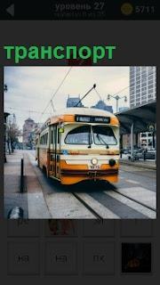 В городе по рельсам идет городской транспорт трамвай, делая периодически остановки, высаживая пассажиров