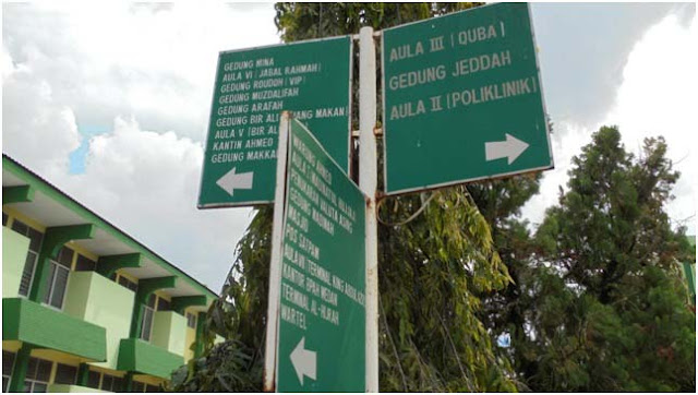 Plang petunjuk ke lokasi masjid, aula, klinik, bank, tempat penukaran uang riyal, wartel