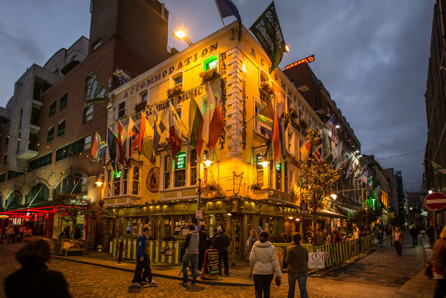 An evening picture of The Oliver St John Gogarty Bar in Temple Bar Dublin with people socialising & passing outside