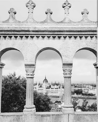 The parliament building is visible across the Danube river through an archway at Fisherman's Bastion
