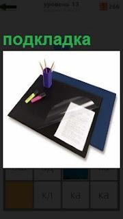 На столе вкладыш на подкладке, куда кладут листок бумаги и маркеры сбоку